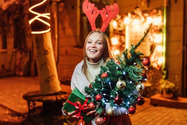 Mooie blonde vrouw met een kerstboom en een cadeau in haar handen lachend