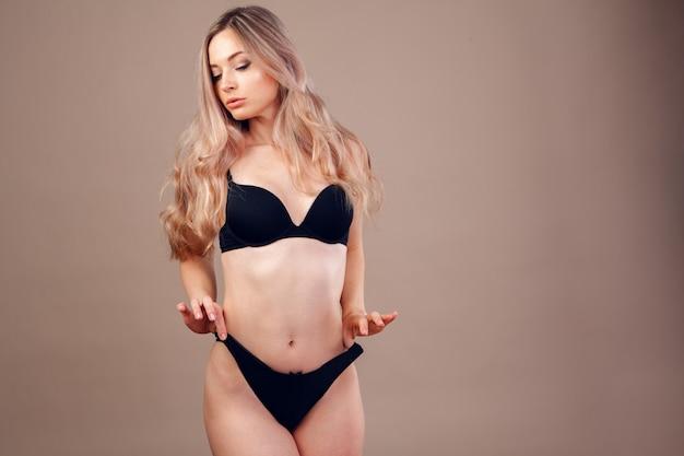 Mooie blonde vrouw met een perfect lichaam in lingerie