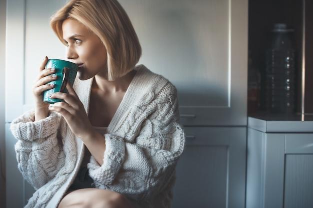 Mooie blonde vrouw met gebreide trui een thee drinken bij het raam en glimlach ergens op zoek