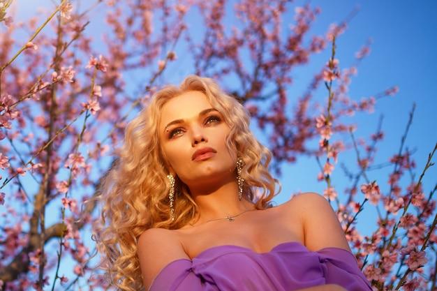 Mooie blonde vrouw met golvend haar poseren met bloeiende perzikbomen tegen de hemel