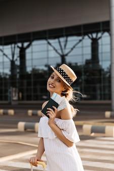 Mooie blonde vrouw met hoed glimlacht oprecht