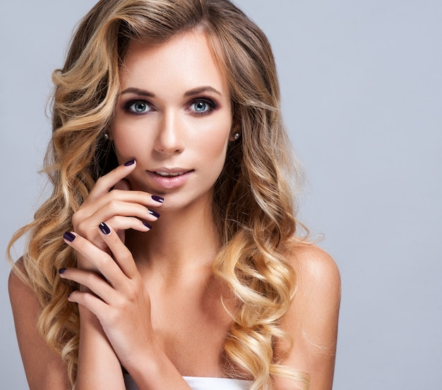 Mooie blonde vrouw met lang krullend haar