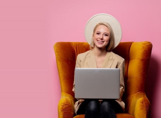 Mooie blonde vrouw met laptopcomputer zit in fauteuil