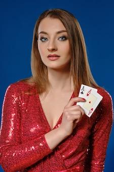 Mooie blonde vrouw met make-up, in rode pailletten jurk toont twee azen, poseren tegen een blauwe achtergrond. gokken entertainment, poker, casino. detailopname.