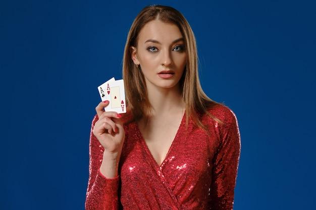 Mooie blonde vrouw met make-up, in rode pailletten jurk toont twee speelkaarten, poseren tegen blauwe achtergrond. gokken entertainment, poker, casino. detailopname.