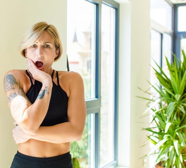 Mooie blonde vrouw met open mond van shock en ongeloof, met hand op wang en arm gekruist, stomverbaasd en verbaasd