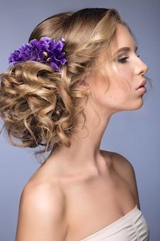 Mooie blonde vrouw met paarse bloemen op haar hoofd
