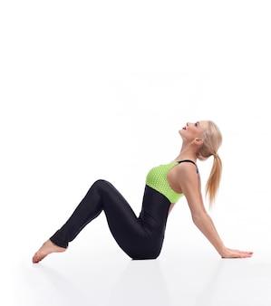Mooie blonde vrouw met perfect gevormde lichaam zittend op de vloer