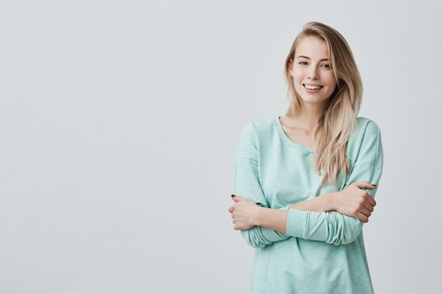 Mooie blonde vrouw met perfecte tanden en gezonde schone huid met rust binnenshuis, gelukkig lachend na het ontvangen van goed positief nieuws. mooie jonge vrouw die zich met gevouwen wapens bevindt