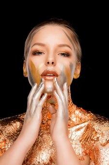 Mooie blonde vrouw met professionele make-up en bladgoud op haar schouders en nek