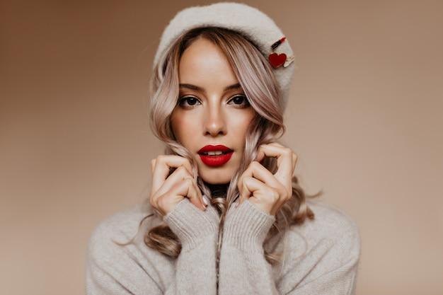 Mooie blonde vrouw met rode lippen die zich op bruine muur bevinden