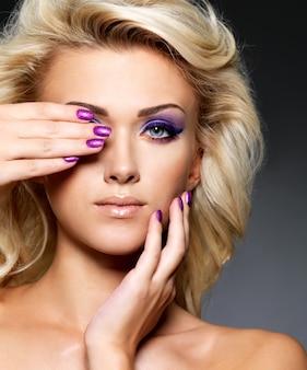 Mooie blonde vrouw met schoonheid paarse manicure en make-up van de ogen. mannequin met krullend kapsel.