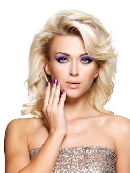 Mooie blonde vrouw met schoonheid paarse manicure en make-up van de ogen.