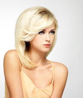 Mooie blonde vrouw met stijl kapsel poseren