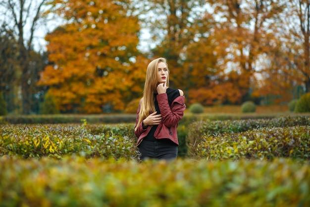 Mooie blonde vrouw met trui en jas poseren in de botanische tuin