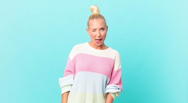 Mooie blonde vrouw met vrolijke en rebelse houding, grappen makend en tong uitsteken