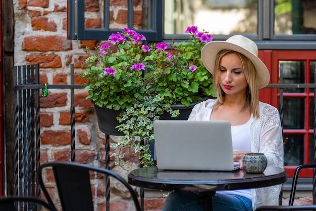Mooie blonde vrouw met zonhoed gekleed in lichte kleren die in openluchtkoffie zitten en met computer werken