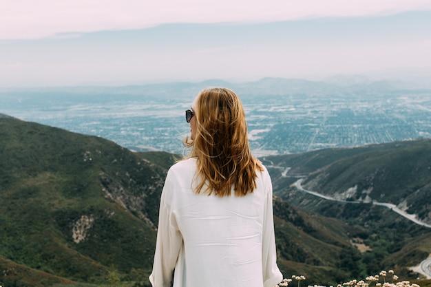 Mooie blonde vrouw met zonnebril en een wit overhemd staande op de top van een heuvel in de natuur