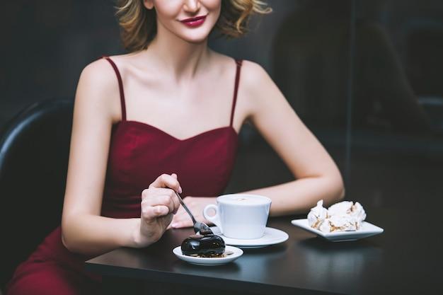 Mooie blonde vrouw model in een rode jumpsuit modieus en elegant met een kopje koffie in het restaurant