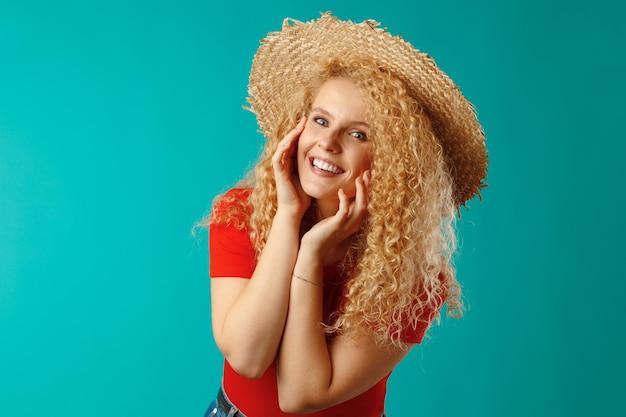 Mooie blonde vrouw model poseren in een strooien hoed tegen blauw