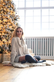 Mooie blonde vrouw naast de kerstboom.