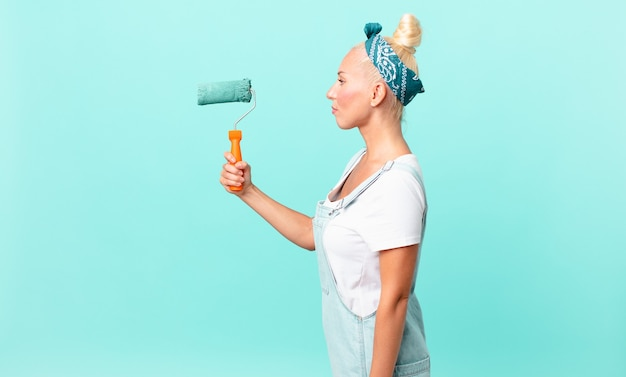 Mooie blonde vrouw op profielweergave denken, fantaseren of dagdromen en een muur schilderen