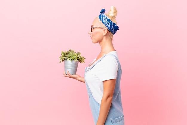 Mooie blonde vrouw op profielweergave denken, verbeelden of dagdromen en een plant vasthouden