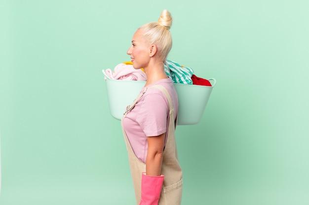 Mooie blonde vrouw op profielweergave denken, verbeelden of dagdromen waskleren concept
