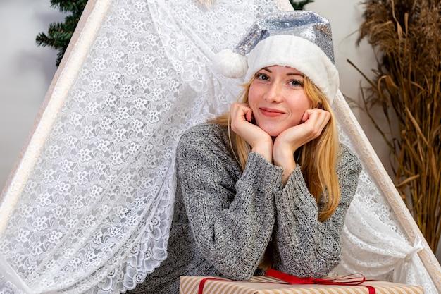 Mooie blonde vrouw opleggen van kerst geschenkdozen dragen gebreide trui en kerstmuts