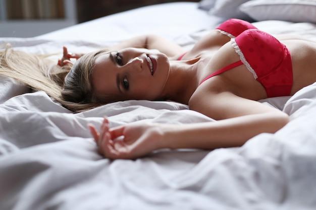 Mooie blonde vrouw poseren in rood ondergoed op bed