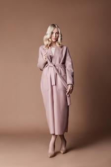 Mooie blonde vrouw poseren in roze jas op beige achtergrond. modeshow kleding, vrouw met lang haar. trendy modieuze herfstjas