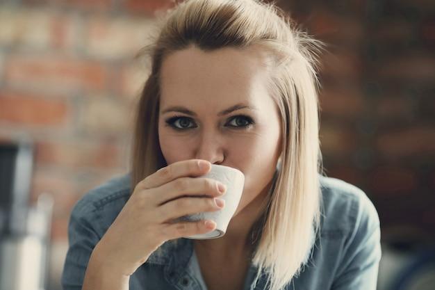 Mooie blonde vrouw poseren met koffiekopje