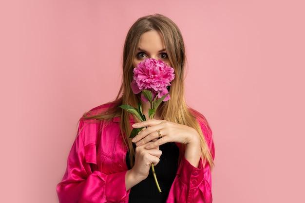 Mooie blonde vrouw poseren met pioenroos in stijlvolle zomeroutfit over roze muur