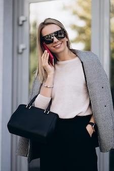 Mooie blonde vrouw praten over telefoon lopen op straat. portret van stijlvolle glimlachende zakenvrouw in donkere casual broek en romige trui. mode concept. vrouwelijke zakelijke stijl. hoge resolutie.
