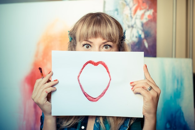 Mooie blonde vrouw schilder glimlachen