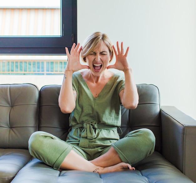 Mooie blonde vrouw schreeuwen in paniek of woede, geschokt, doodsbang of woedend, met de handen naast het hoofd