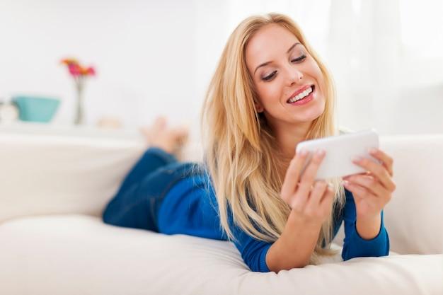 Mooie blonde vrouw sms-berichten op de bank