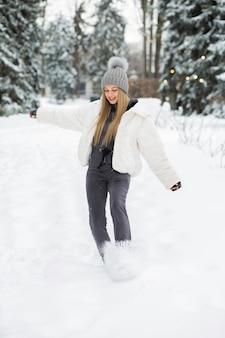 Mooie blonde vrouw speelt met sneeuw in het bos