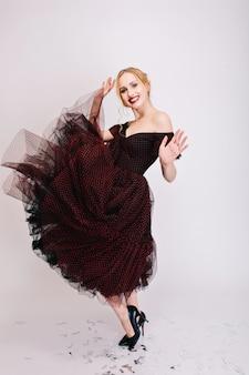 Mooie blonde vrouw spinnen in dans, rok twirling, plezier op feestje, genieten van schieten. het dragen van een donzige zwarte jurk en elegante zwarte schoenen met hakken. .