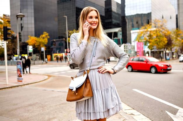 Mooie blonde vrouw spreekt door haar telefoon op straat in de buurt van stedelijke gebouwen, grijze trui en vrouwelijke rok
