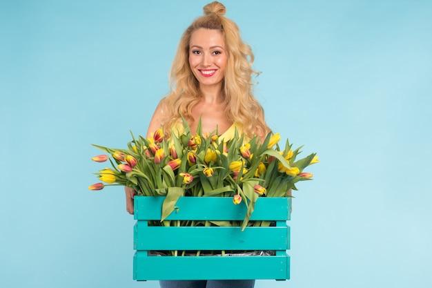 Mooie blonde vrouw tuinman bedrijf doos met tulpen op blauwe achtergrond