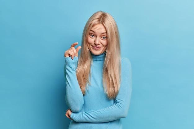 Mooie blonde vrouw vormt een klein onzichtbaar item met vingers toont een kleine hoeveelheid van iets dat spreekt over haar kleine prestatie gekleed in een casual coltrui
