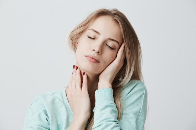 Mooie blonde vrouw vormt met gesloten ogen, raakt haar hoofd met handen, heeft dromerige gezichtsuitdrukking.