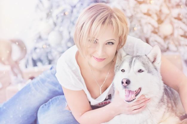 Mooie blonde vrouw zit met husky hond in de buurt van kerstboom. gelukkig wintervakantieconcept.