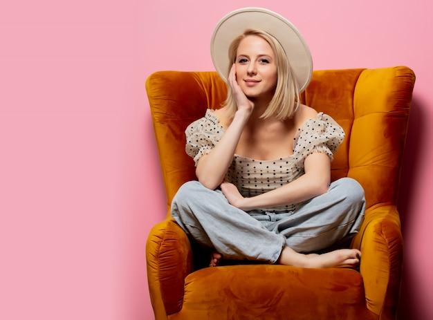 Mooie blonde vrouw zitten in een vintage fauteuil op roze muur