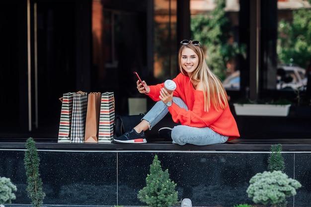 Mooie blonde vrouw zittend op straat en omringd door boodschappentassen en kijken op telefoon. mode straat concept.