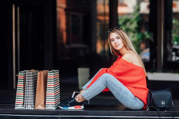 Mooie blonde vrouw zittend op straat en omringd door boodschappentassen.