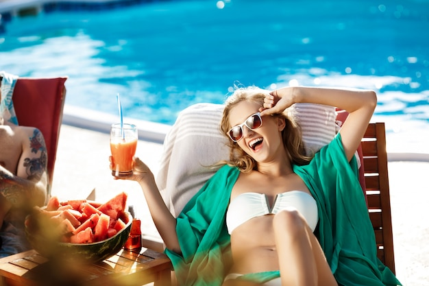 Mooie blonde vrouw zonnen, cocktail drinken, liggend in de buurt van zwembad