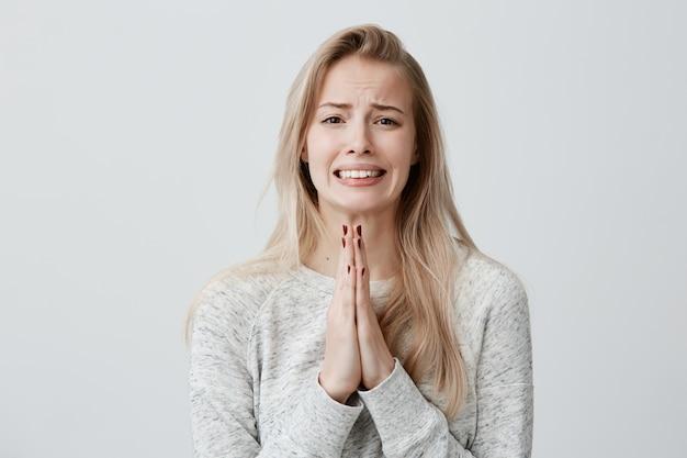 Mooie blonde vrouwelijke balde tanden met bedelende blik met handpalmen tegen elkaar gedrukt, vragend om medelijden