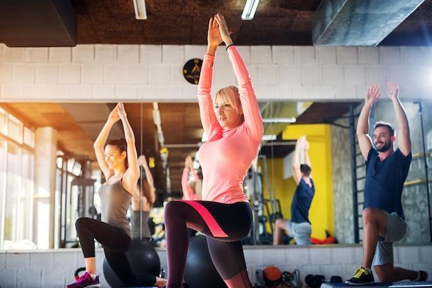 Mooie blonde vrouwelijke gymnastiekinstructeur die sommige oefeningen toont aan haar groep.